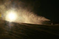 Skifahrer nahe einer Schneekanone, die Pulverschnee macht Alpenskiort Lizenzfreies Stockfoto