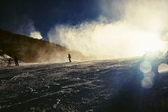 Skifahrer nahe einer Schneekanone, die Pulverschnee macht Alpenskiort Lizenzfreie Stockfotos