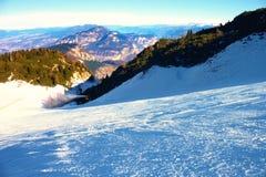 Skifahrer nahe einer Schneekanone, die Pulverschnee macht Alpenskiort Stockfotografie