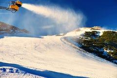 Skifahrer nahe einer Schneekanone, die Pulverschnee macht Alpenskiort Lizenzfreie Stockfotografie