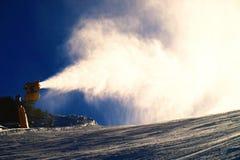 Skifahrer nahe einer Schneekanone, die Pulverschnee macht Alpenskiort Stockbilder
