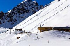 Skifahrer reiten den Hintergrund von mächtigen Bergen lizenzfreies stockbild