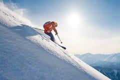 Skifahrer reitet freeride auf Pulverschnee sich neigen unten gegen das backd Stockbild