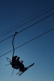 Skifahrer silhouettieren auf Kabelbahn Stockbild