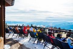 Skifahrer sitzen auf Stühlen nahe einem Restaurant auf einen Berg Leute im Skianzugrest und -getränk lizenzfreie stockbilder