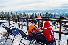 Skifahrer sitzen auf Stühlen nahe einem Restaurant auf einen Berg Leute im Skianzugrest und -getränk stockfoto