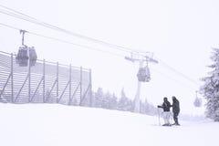Skifahrer steht nahe der Spitze eines Skiberges Lizenzfreie Stockbilder