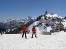 Skifahrer und alpines Dorfpanorama Lizenzfreie Stockfotos