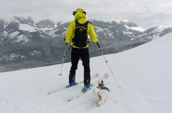 Skifahrer und sein Hund, die eine Minute nehmen, um die Ansicht zu bewundern Lizenzfreies Stockfoto