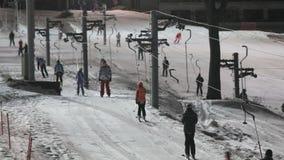 Skifahrer und Snowboarder auf einem Skiaufzug stock video footage