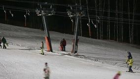 Skifahrer und Snowboarder auf einem Skiaufzug stock footage