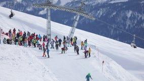 Skifahrer und Snowboarder reiten in das Skiort Auf dem zweiten Plan ist Sesselbahn stock video