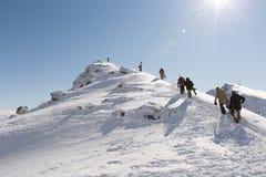 Skifahrer und Snowboarder wandern auf die Oberseite des Remarkables Stockbilder