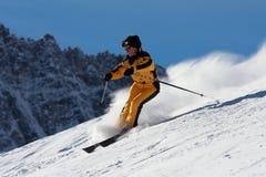 Skifahrerfrau in der gelben Suite, die unten auf Steigung sich verschiebt Lizenzfreie Stockfotografie