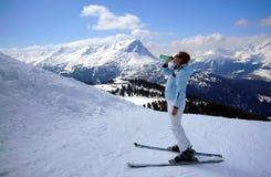 Skifahrerfrau, die Mineralwasser trinkt Lizenzfreie Stockbilder
