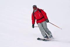 Skifahrermann, der unten von der schneebedeckten Winterrücksortierung MO läuft Lizenzfreies Stockfoto