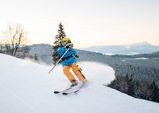 Skifahrermann im Schneepulver produziert das Bremsen auf der Steigung des Berges lizenzfreie stockbilder