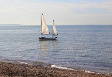 A Skiff. This photo shows a small twin sailed boat crewless and anchored off of the Whitstable coast Stock Image