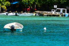 Skiff at anchor in Caribbean Cove. Skiff at anchor in front of sandy beach in British Virgin Islands Stock Photos