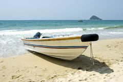 Skiff  on the beach. A single skiff on the seashore,blue sea and clean air Royalty Free Stock Images