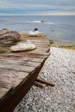 Skiff boat on stone beach by the ocean. With stones on boat cover Royalty Free Stock Images