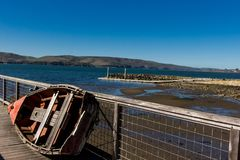Skiff leaning on a dock rail over looking Tomales Bay. On a beautiful sunny day with blue sky Stock Photo
