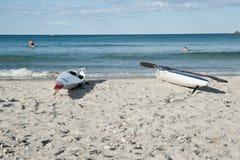 Skiffs auf Strand mit Surfern im Hintergrund. Stockfotografie