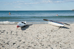 Skiffs on beach with surfers in background. Stock Photography