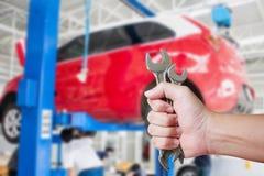 Skiftnyckel för innehav för bilmekaniker på bilreparationsgaraget Arkivbild