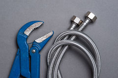 Skiftnyckel och flätad rostfritt stålvattenslang Arkivbild