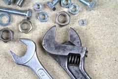 Skiftnyckel, skiftnyckel och olika bultar och muttrar Arkivbilder