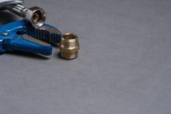 Skiftnyckeln, nippeln och flätat rostfritt stålvatten vattnar med slang Royaltyfri Fotografi