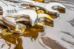 Skiftnycklar muttrar - och - bultar som befläckas med motorisk olja Fotografering för Bildbyråer