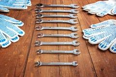 Skiftnycklar och funktionsdugliga handskar på en träbakgrund Arkivfoton