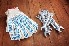 Skiftnycklar och funktionsdugliga handskar på en träbakgrund Royaltyfria Bilder