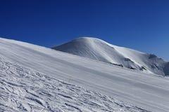 Skihelling en blauwe hemel Stock Fotografie
