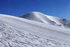 Skihelling en blauwe wolkenloze hemel in aardige de winterdag Royalty-vrije Stock Fotografie