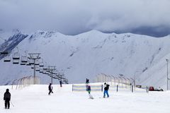Skihelling met skiërs en snowboarders in avond Stock Foto's