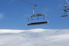 Skihelling, stoeltjeslift bij de skitoevlucht en blauwe hemel met dalend Sn Royalty-vrije Stock Afbeelding