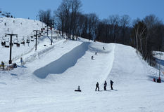 Skihill with a halfpipe run. Ski lift and a halfpipe run with snowboarders Stock Photos