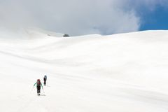 Skiiers ascending mountain slope Royalty Free Stock Photography