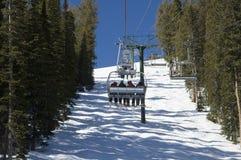 Skiiers die omhoog stoeltjeslift berijdt stock afbeeldingen