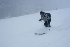 Skiing. Man skiing fast on a foggy day with a hard snow falling Royalty Free Stock Photography