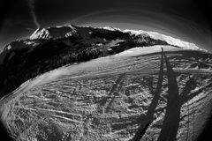 Skiing action 5. Skiing at its best. Fisheye shot taken in the middle of the slope, showing skier, slope, and vista Stock Photo