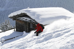 Skiing backcountry blockhouse. Skier skies backcountry with blockhouse in the background Stock Photography