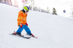 Skiing boy in ski mask, helmet on mountain slope Royalty Free Stock Images