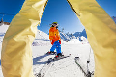 Skiing boy view between the legs of grown-up Stock Image