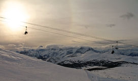 Skiing in the Canadian Rockies. Scenic view of a chairlift above a ski run with hazy late afternoon sun in the Canadian Rockies near Banff, Alberta Stock Images