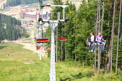 Skiing chair lift. Chair lift in Carpathian Mountains with people Stock Photo
