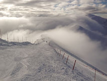 Skiing in the clouds. Ski slope on a mountainridge where the clouds are passing by. Kasprowy Wierch in the Tatra mountains, Zakopane, Polen royalty free stock photo